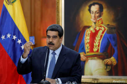 Venezuela's President Nicolas Maduro holds a copy of the National Constitution while he speaks during a news conference at Miraflores Palace in Caracas, Venezuela, Jan. 9, 2019.