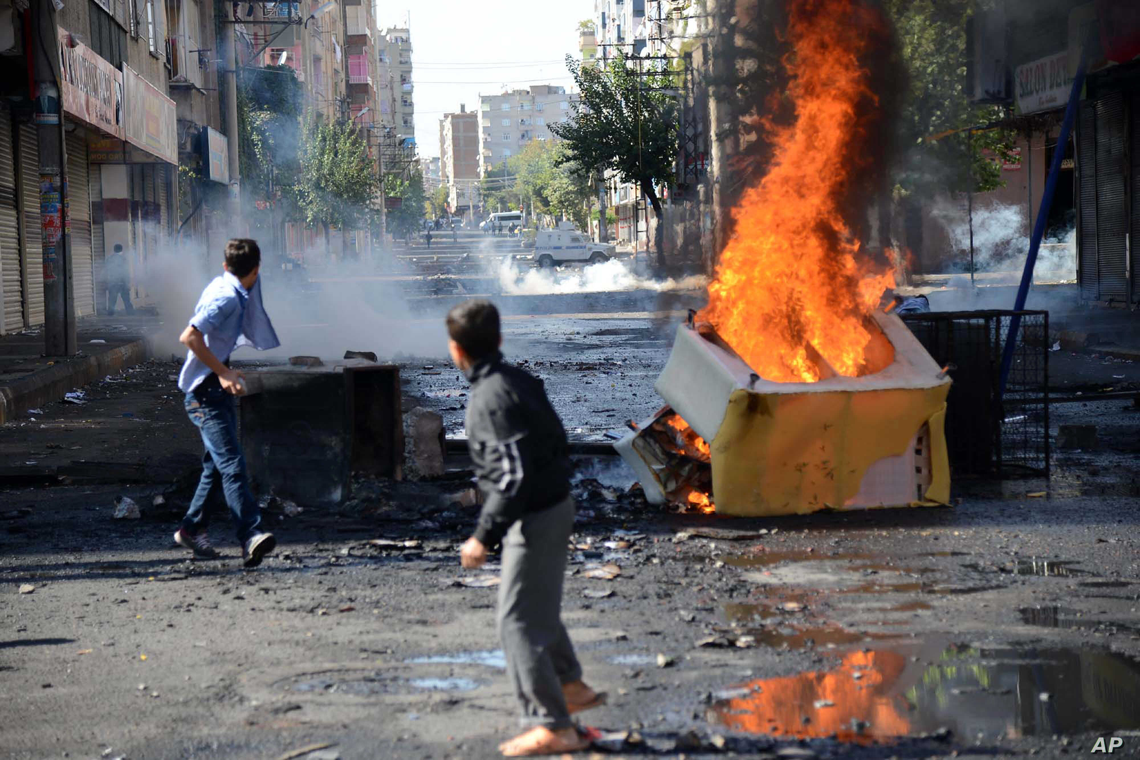 FILE - With tanks in the background, youths set fire to barricades in Diyarbakir, Turkey, hours after Kurds protesting the Islamic State advance on Kobani, Syria, had clashed with police, Oct. 8, 2014.