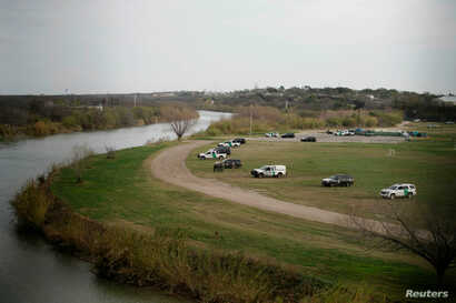 U.S. border patrol cars are seen through the fence of the bridge connecting Eagle Pass, Texas, with Piedras Negras, Mexico, near the banks of Rio Bravo, from Piedras Negras, Mexico, Feb. 7, 2019.