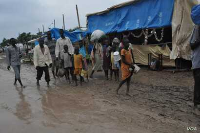 People walk along dirt roads that have been turned into streams of mud by the rains, in the UNMISS base in Malakal, South Sudan, where 19,000 people have sought shelter from months of fighting.