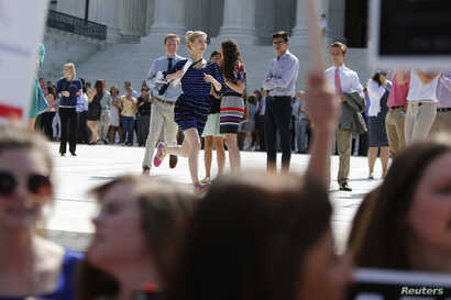 Reporters run from the courthouse with paper copies of the U.S. Supreme Court decision for the Hobby Lobby, in Washington, June 30, 2014.