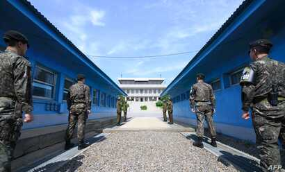 South Korean soldiers (front) and North Korean soldiers (rear) stand guard before the military demarcation line on the each side of the truce village of Panmunjom in the Demilitarized zone (DMZ) dividing the two Koreas.