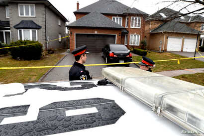 Police officers wait for a search warrant in front of the home of Alek Minassian, in Richmond Hill, Ontario, April 25, 2018.