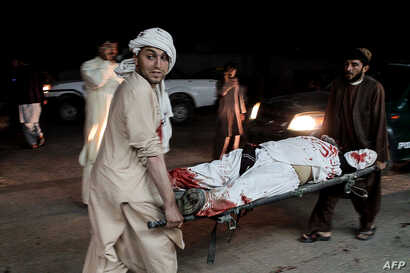 Afghan men carry a wounded man into a hospital following a car bomb explosion in Lashkargah, capital of Helmand province, Afghanistan, March 23, 2018. The attack prompted locals to stage an anti-war protest.