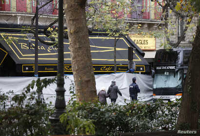 People walk past the screened-off facade of the Bataclan Cafe and its adjoining concert hall the day after a series of deadly attacks in Paris, Nov. 14, 2015.