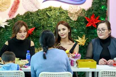 This photo taken on December 2, 2018 shows transgender make-up artist Solongo Batsukh (C) chatting at a salon in Ulaanbaatar, the capital of Mongolia.
