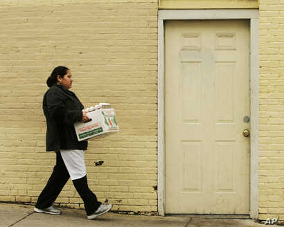 FILE -- Maria Reyes, originally from El Salvador, carries supplies into the La Pupusa Guanaca restaurant in the Jamaica Plain neighborhood of Boston, Massachusetts.