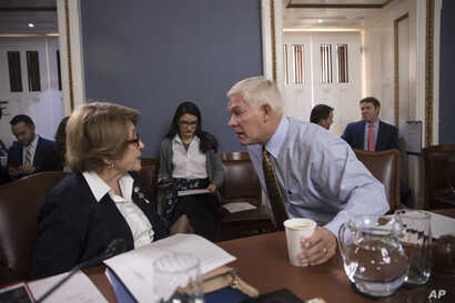 House Rules Committee Chairman Pete Sessions, R-Texas (C), confers with Rep. Louise Slaughter, D-N.Y., the top Democrat, as the panel meets on Capitol Hill in Washington, Dec. 21, 2017.