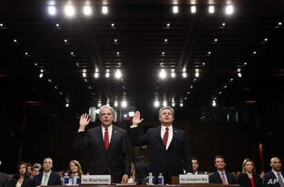 Department of Justice Inspector General Michael Horowitz, left, and FBI Director Christopher Wray are sworn in during a hearing of the Senate Judiciary Committee to examine Horowitz's report of the FBI's Clinton email probe, on Capitol Hill, June 18,...