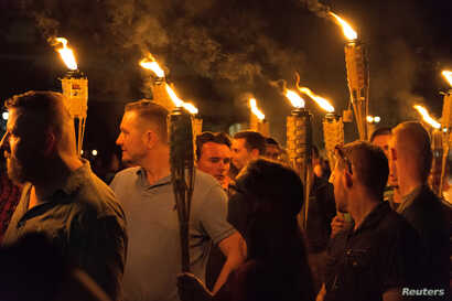 "White supremacists carry torches on the grounds of the University of Virginia, on the eve of a planned ""Unite the Right"" rally in Charlottesville, Virginia, Aug. 11, 2017."