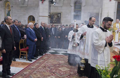 Palestinian President Mahmoud Abbas, second from left in front, attends a Christmas midnight mass at Saint Catherine's Church, in the Church of the Nativity, traditionally recognized by Christians to be the birthplace of Jesus Christ, in the West Ban...