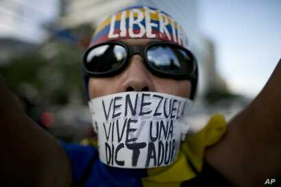"A woman wears a banner over her mouth with a message that reads in Spanish: ""Venezuela lives in a dictatorship"" during a protest, in Caracas, March 31, 2017."