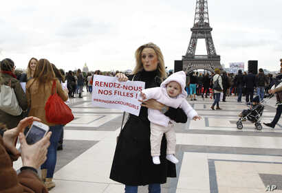 "A woman holds her baby and a poster reading ""Bring Back our Girls"" during a rally to support the release of the kidnapped Nigerian girls at the Trocadero, in front of the Eiffel Tower, in Paris on May 13, 2014."