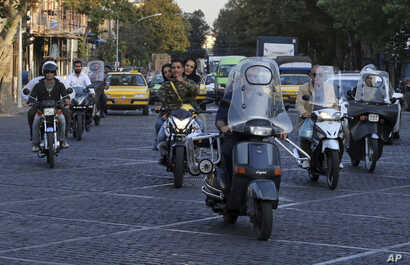 People ride motorcycles in downtown Tehran, Iran, Oct. 8, 2017.