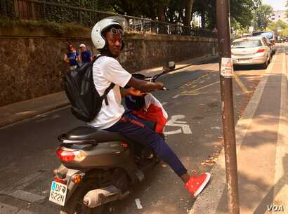 A French fan is all geared up for the game in national colors, in Paris, France, July 15, 2018. (L. Bryant/VOA)