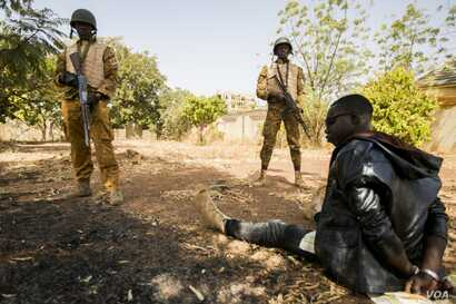 Burkinabe soldiers guard a terrorist during a simulated terrorist attack in Ouagadougou, Burkina Faso, Feb. 27, 2019, during Flintlock 2019. The Burkinabe army was responsible for cordoning off the surrounding area and securing any surviving terroris...