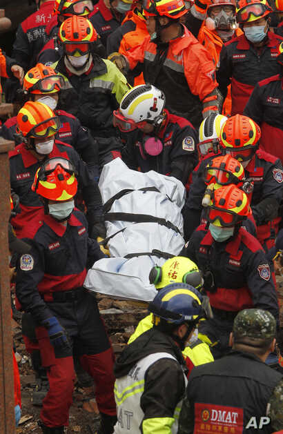 Rescuers carry a victim recovered from a collapsed building following a strong earthquake in Hualien County, eastern Taiwan, Feb. 8, 2018. A magnitude 6.4 earthquake struck late Tuesday night caused several buildings to cave in and tilt dangerously. ...