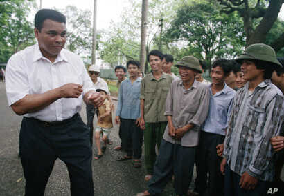 FILE - Muhammad Ali, left, assumes his former fighting stance while joking around with Vietnamese people on the path outside of Ho Chi Minh's former home in Hanoi, Vietnam, May 11, 1994. Ali visited the families of American and Vietnamese servicemen ...