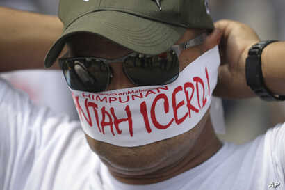 """A protester covers his face with headbands reading """"No to ICERD"""" during a rally to celebrate the government's decision not to ratify a U.N. anti-discrimination convention called ICERD at Independent Square in Kuala Lumpur, Malaysia, Dec. 8, 2018. ICE..."""
