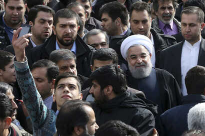 An Iranian man, at left, takes a selfie while trying to have President Hassan Rouhani, right with white turban, in his picture in a rally commemorating the 37th anniversary of the Islamic revolution, in Tehran, Feb. 11, 2016.