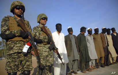 Pakistani paramilitary soldiers guard suspects arrested during a search operation in Shah Kass, an area of Pakistan's Khyber tribal region along the Afghan border, March 3, 2017.