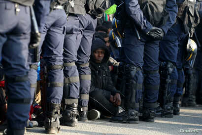 """French police stand near as migrants wait in front of a processing center to be registered on the second day of their evacuation and transfer to reception centers in France, during the dismantlement of the camp called """"the jungle"""" in Calais, France, ..."""