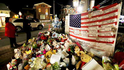A U.S. flag displays the name of 26 victims killed last week when a man opened fired at Sandy Hook Elementary School stands at a makeshift memorial in the Sandy Hook village of Newtown, Conn., December 20, 2012.
