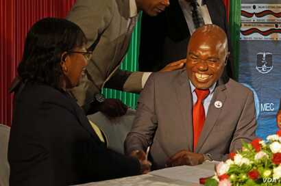 Opposition Malawi Congress Party General Secretary, Eisenhower Mkaka, cracks jokes with MEC chairperson Jane Ansah as he signed a code of conduct,Tuesday in Lilongwe.