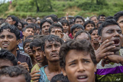 Rohingya Muslims, who crossed over from Myanmar into Bangladesh, wait for their turn to collect aid near Balukhali refugee camp, Bangladesh, Sept. 20, 2017.