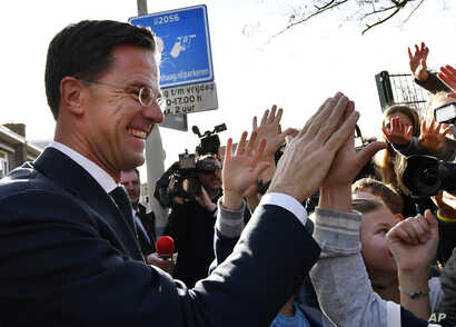 Dutch Prime Minister Mark Rutte gives 'high five' to children after casting his vote for the Dutch general election in The Hague, Netherlands, March 15, 2017.