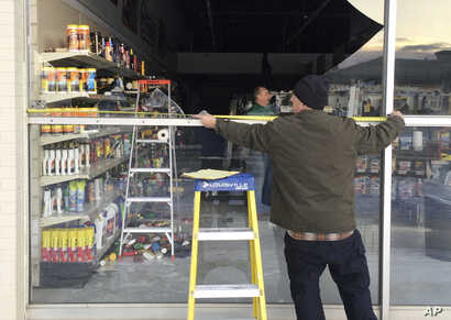 Dennis Keeling measures for a broken window at an auto parts store in Anchorage, on Nov. 30, 2018.