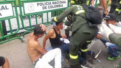 A Colombian police officer helps men who were hurt in clashes at the Simon Bolivar Bridge on the Colombia-Venezuela border.