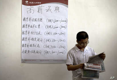 FILE - Chinese man reads the employment newsletters at a job fair held at the China International Exhibition Center in Beijing.