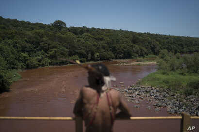 Hayo, chief of the Pataxo Ha-ha-hae indigenous community, stands over the Paraopeba River on a rail bridge near his village in Brumadinho, Brazil, Jan. 29, 2019.