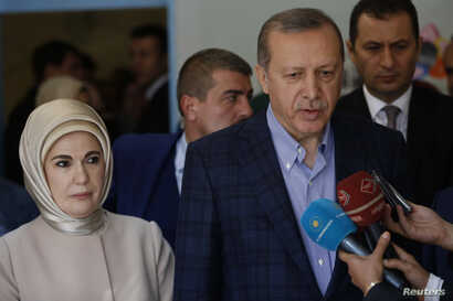 Turkish President Tayyip Erdogan, accompanied by his wife Emine Erdogan, speaks to media after voting in Istanbul, Nov. 1, 2015.