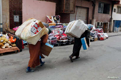 FILE - Moroccan women carry goods after crossing the border from Spain's North African enclave of Melilla into Moroccan settlement of Beni Ansar, in Beni Ansar, Morocco, July 18, 2017.