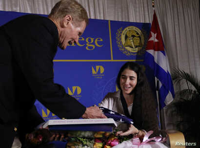 FILE - US Senator Bill Nelson (D-FL) presents a U.S. flag to Yoani Sanchez, the best-known dissident blogger from Cuba, after she spoke at the Freedom Tower in Miami, Florida April 1, 2013.