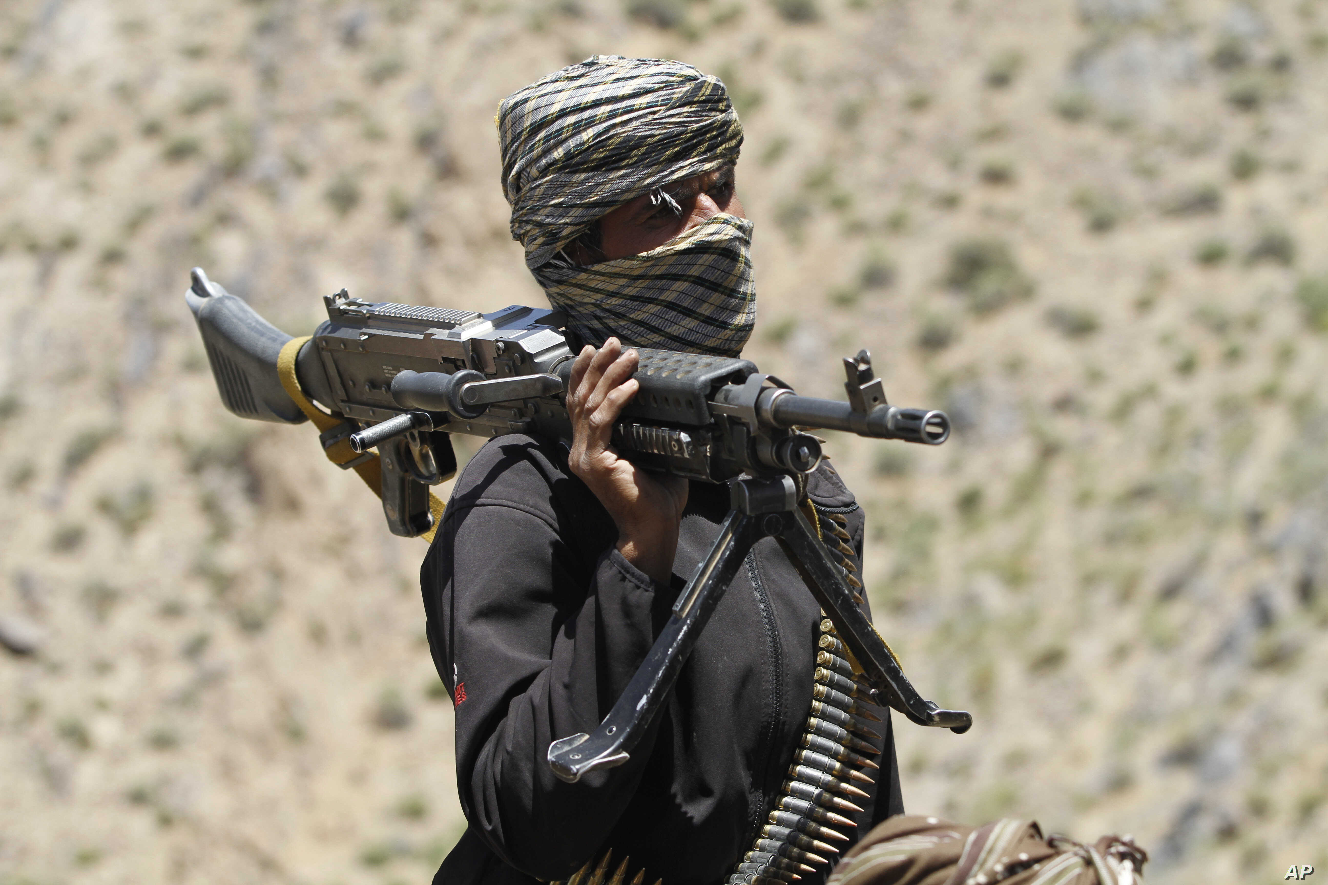 FILE - In this May 27, 2016 file photo, a member of a breakaway faction of the Taliban fighters guards a gathering in Shindand district of Herat province, Afghanistan.