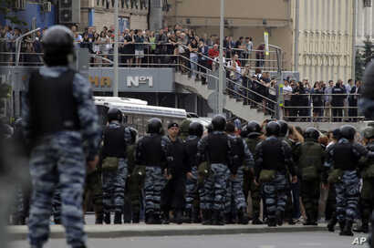 Protesters, monitored by scores of policemen, take part in a demonstration in downtown Moscow, Russia, June 12, 2017.