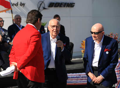 """Astronaut Jim Lovell, center, speaks, accompanied by fellow astronaut Tom Stafford, during the ribbon cutting ceremony for the """"Heroes and Legends"""" exhibit at the Kennedy Space Center Visitor Complex in Florida,"""