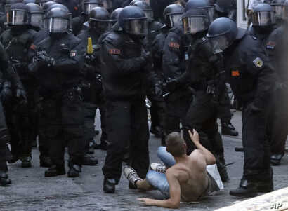 A man, sitting on the ground, gestures as police officers approach during a protest against the G-20 summit in Hamburg, Germany, July 7, 2017.