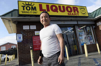 James Oh, owner of Tom's Liquors, poses outside his store at the intersection of Florence and Normandie,  April 18, 2017, in Los Angeles.