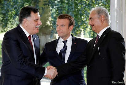 FILE PHOTO: French President Emmanuel Macron stands between Libyan Prime Minister Fayez al-Sarraj, lefr, and General Khalifa Haftar, commander in the Libyan National Army), who shake hands after talks over a political deal to help end Libya's crisis ...