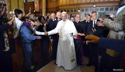 Pope Francis greets parishioners, immigrants and clients of Catholic Charities, as he arrives at St. Patrick's Church, in Washington, Sept. 24, 2015.