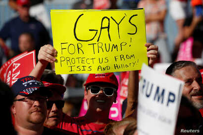 """A person holds up a """"Gays for Trump""""  sign as then-Republican presidential nominee Donald Trump holds a campaign event in Orlando, Fla., Nov. 2, 2016."""