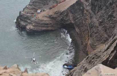 A helicopter helps rescue workers at the scene after a bus crashed with a truck and careened off a cliff along a sharply curving highway north of Lima, Peru, Jan. 2, 2018.