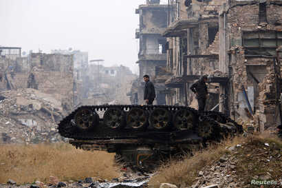 Forces loyal to Syria's President Bashar al-Assad stand atop a damaged tank near Umayyad mosque, in the government-controlled area of Aleppo, Syria, during a media tour Dec. 13, 2016.