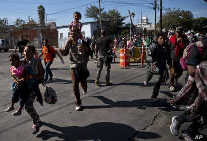 Migrants run toward the U.S. after breaking past a line of Mexican police at the Chaparral border crossing in Tijuana, Mexico, Nov. 25, 2018, near the San Ysidro, California, entry point.