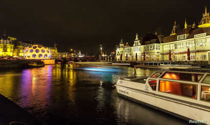 FILE - A tourist boat passes on a canal in Amsterdam, Dec. 6, 2013.