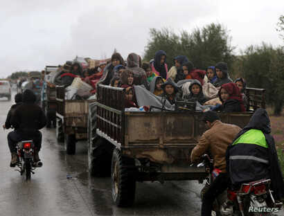 People sit in a truck with their belongings in the north east of Afrin, Syria, March 15, 2018.